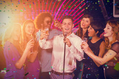 Composite image of group of friends singing song together in bar. Group of friends singing song together in bar against flying colours Stock Photo
