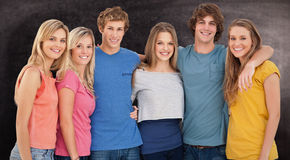Composite image of a group of friends smiling and holding each other Stock Photo
