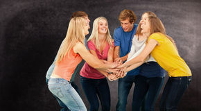 Composite image of group of friends about to cheer with their hands stacked Royalty Free Stock Photo