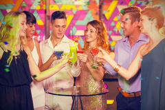 Composite image of group of friends toasting glass of cocktail in bar stock photography