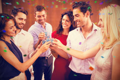 Composite image of group of friends toasting shots. Group of friends toasting shots against flying colours royalty free stock image