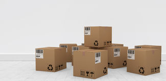 Composite image of group of graphic cardboard boxes. Group of graphic cardboard boxes against gray flooring and wall Royalty Free Stock Photography