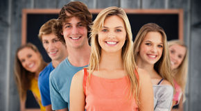 Composite image of group standing behind one another at varied angles. Group standing behind one another at varied angles against blackboard with copy space on Stock Photography