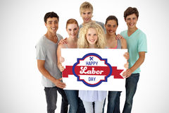 Composite image of group of teenagers holding a blank card. Group of teenagers holding a blank card against digital composite image of happy labor day banner stock image