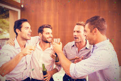 Composite image of group of young men having drinks Royalty Free Stock Image