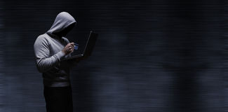 Composite image of hacker using laptop while holding credit card stock images