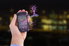 Composite image of hand of businessman showing smartphone 3d. Hand of businessman showing smartphone against illuminated city by lake 3d Royalty Free Stock Photography