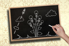 Composite image of hand drawing light bulb plant with chalk Royalty Free Stock Images