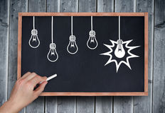Composite image of hand drawing light bulbs with chalk Stock Images