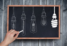 Composite image of hand drawing light bulbs with chalk Stock Photo