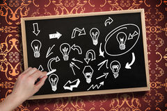 Composite image of hand drawing light bulbs with chalk Royalty Free Stock Images