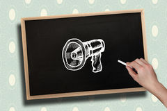 Composite image of hand drawing megaphone with chalk