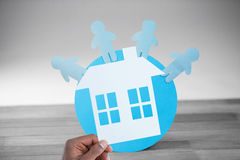 Composite image of hand holding a house in paper Stock Photography