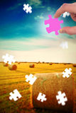 Composite image of hand holding jigsaw piece Royalty Free Stock Photos