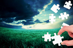 Composite image of hand holding jigsaw piece Royalty Free Stock Images