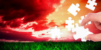 Composite image of hand holding jigsaw piece Stock Image