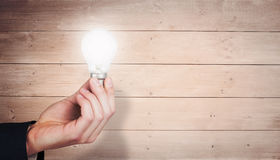 Composite image of hand holding light bulb Royalty Free Stock Images