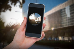Composite image of hand holding mobile phone against white background. Hand holding mobile phone against white background against front side of buildings Royalty Free Stock Images