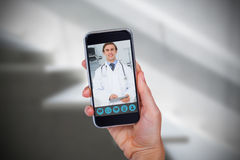 Composite image of hand holding mobile phone against white background. Hand holding mobile phone against white background against sterile bedroom Stock Photo