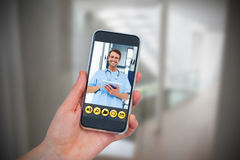 Composite image of hand holding mobile phone against white background. Hand holding mobile phone against white background against wheelchair in the corridor Royalty Free Stock Photo