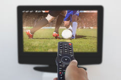 Composite image of hand holding remote and changing channel. Hand holding remote and changing channel against football players tackling for the ball on pitch vector illustration