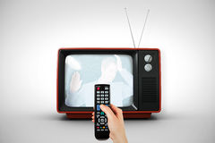 Composite image of hand holding remote control Royalty Free Stock Photo