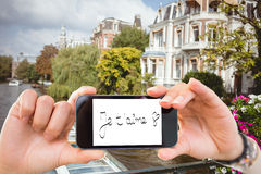 Composite image of hand holding smartphone showing je taime Stock Image