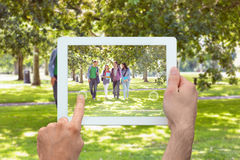 Composite image of hand holding tablet pc. Hand holding tablet pc against froup of college students walking in the park royalty free stock images