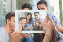 Composite image of hand holding tablet pc. Hand holding tablet pc against happy students looking at smartphone outside on campus Royalty Free Stock Images