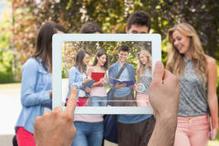 Composite image of hand holding tablet pc. Hand holding tablet pc against happy students walking and chatting outside Stock Photo