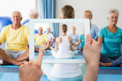 Composite image of hand holding tablet pc. Hand holding tablet pc against instructor performing yoga with seniors Royalty Free Stock Photos