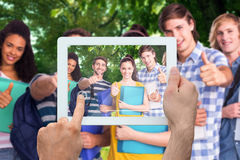 Composite image of hand holding tablet pc. Hand holding tablet pc against park Stock Images