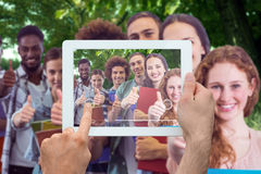 Composite image of hand holding tablet pc. Hand holding tablet pc against park on sunny day Royalty Free Stock Photography
