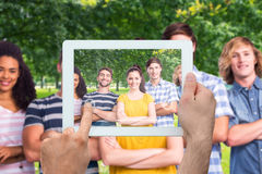 Composite image of hand holding tablet pc. Hand holding tablet pc against park on sunny day Royalty Free Stock Photo