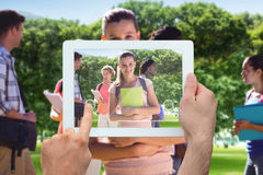 Composite image of hand holding tablet pc. Hand holding tablet pc against park on sunny day Stock Images