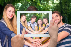 Composite image of hand holding tablet pc. Hand holding tablet pc against park on sunny day Royalty Free Stock Image
