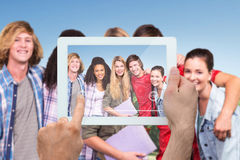 Composite image of hand holding tablet pc. Hand holding tablet pc against park on sunny day Stock Photography