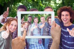 Composite image of hand holding tablet pc. Hand holding tablet pc against park on sunny day Stock Photo