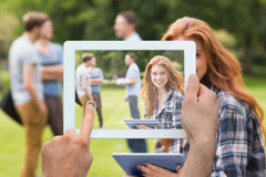 Composite image of hand holding tablet pc. Hand holding tablet pc against pretty student studying outside on campus Stock Images