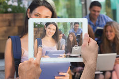 Composite image of hand holding tablet pc. Hand holding tablet pc against pretty student using her tablet pc on campus Stock Images