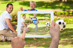 Composite image of hand holding tablet pc. Hand holding tablet pc showing father watching son kicking football Stock Images