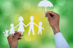 Composite image of hand holding an umbrella and a family in paper Stock Photography