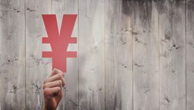 Composite image of hand holding yen sign Royalty Free Stock Image