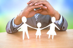 Composite image of hand protecting a family in paper Royalty Free Stock Photo