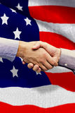 Composite image of hand shake in front of wires. Hand shake in front of wires against black wall Stock Photography