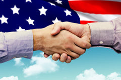 Composite image of hand shake in front of wires. Hand shake in front of wires against blue sky Stock Photo