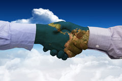Composite image of hand shake in front of wires. Hand shake in front of wires against bright blue sky with clouds Royalty Free Stock Photos