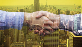 Composite image of hand shake in front of wires. Hand shake in front of wires against city skyline Royalty Free Stock Photo