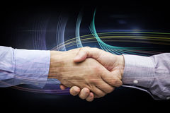 Composite image of hand shake in front of wires. Hand shake in front of wires against futuristic glowing lines on black background Royalty Free Stock Image