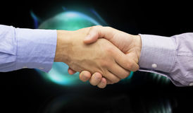 Composite image of hand shake in front of wires. Hand shake in front of wires against glowing light bulb Stock Images